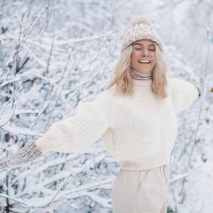 Beauty-Tipps für den Winter: Hello, Miss Frosty!: Junge Frau lächelnd in verschneiter Natur