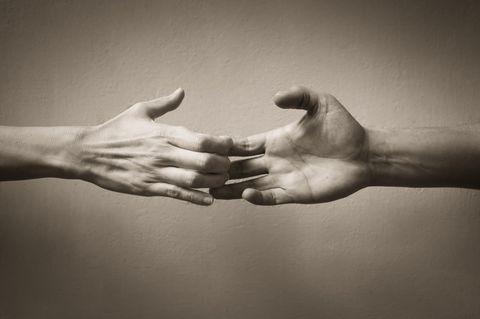 Loslassen lernen: Zwei Hände in schwarz-weiß halten aneinander fest