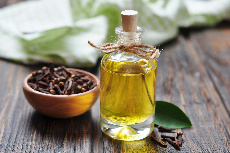 Nelkenöl: Öl in Flasche neben Nelkenblatt
