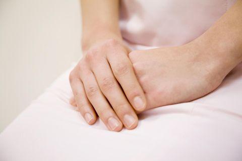 Lichen Sclerosus: Symptome der Hauterkrankung: Frau hält Hände verschränkt auf dem Schoß