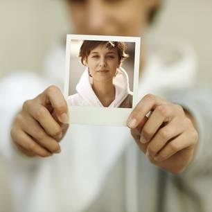 Typveränderung wagen: Das macht es mit mir: Frau mit ihrem Bild in der Hand
