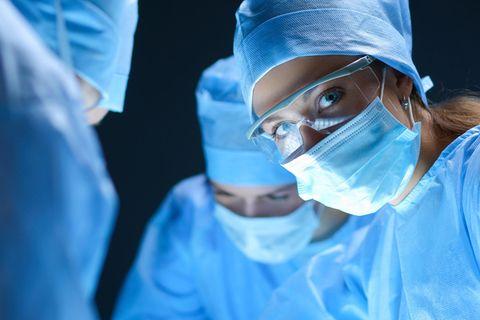 Eine Chirurgin trägt während ihrer Arbeit Mundschutz und OP-Kleidung