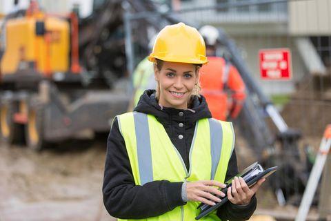Bauleiter: Bauleiterin mit Schutzhelm auf der Baustelle
