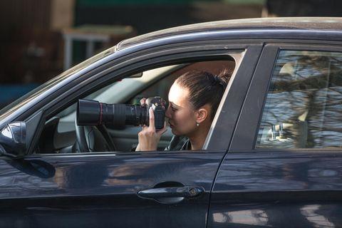 Detektiv: Detektivin sitzt in ihrem Auto und macht heimlich Fotos