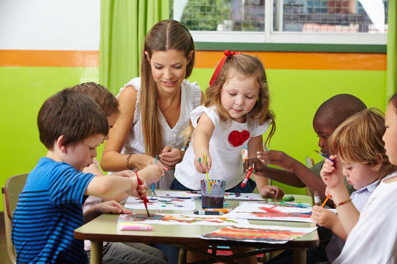 Erzieherin malt gemeinsam mit Kindern