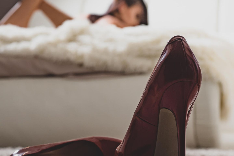 Fetisch: Im Hintergrund liegt eine Frau im Bett, im Vordergrund stehen High Heels