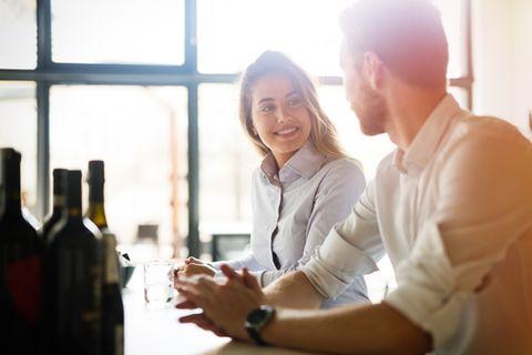 Verliebt in Kollegen: Junge Frau und junger Mann sehen sich fröhlich an