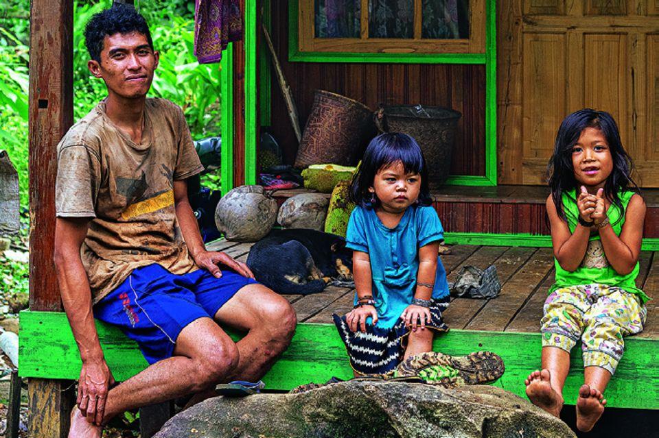 Reisetipps Borneo: Wie aus einer anderen Zeit: Mann und zwei kleine Kinder sitzen auf Veranda