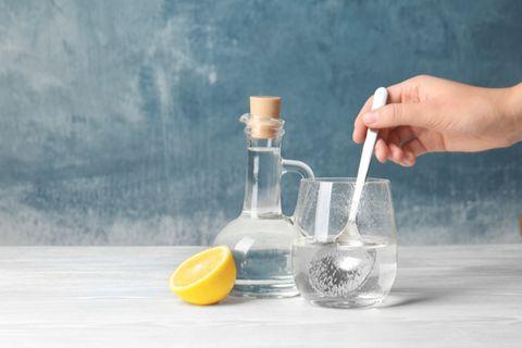 Klarspüler selber machen: Glasflasche und Glas, in das etwas eingerührt wird