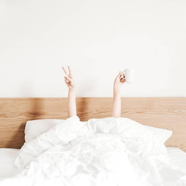 Horoskop: Eine Frau liegt im Bett und streckt nur ihre Hände in die Luft