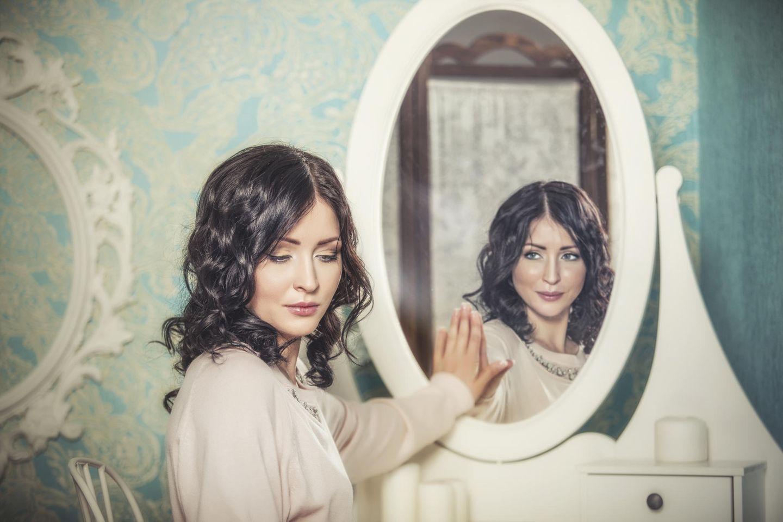 Frau mit Hand am Spiegel mit unterschiedlichem Spiegelbild