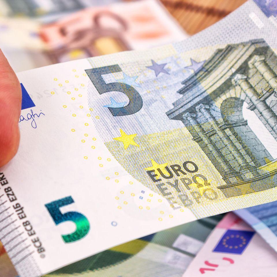 5-Euro-Schein vor Stapel anderer Scheine