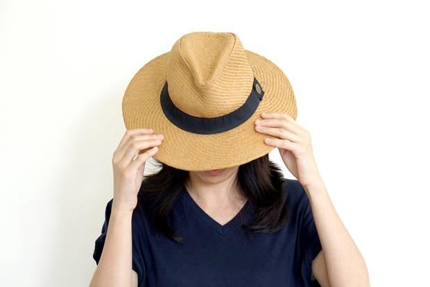Frau verdeckt ihr Gesicht mit Hut