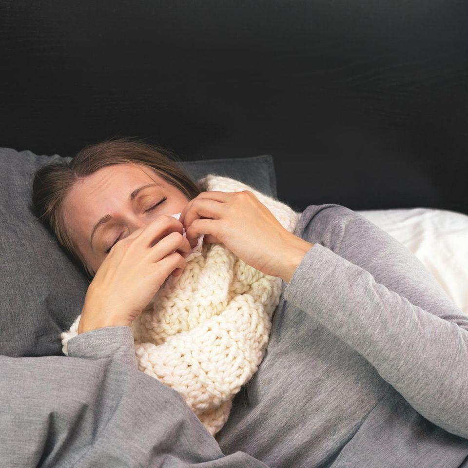 Erkältete Frau mit Schal im Bett
