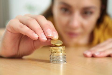 """Sparen mit kleinen Beträgen: """"3 Euro? Das lohnt sich!"""": Frau stapelt Münzgeld"""