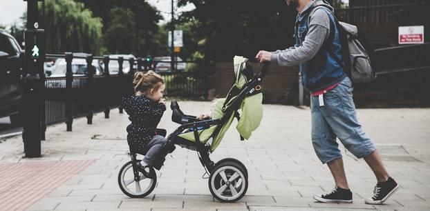 Neue Väter-Generation: Vater schiebt Kinderwagen