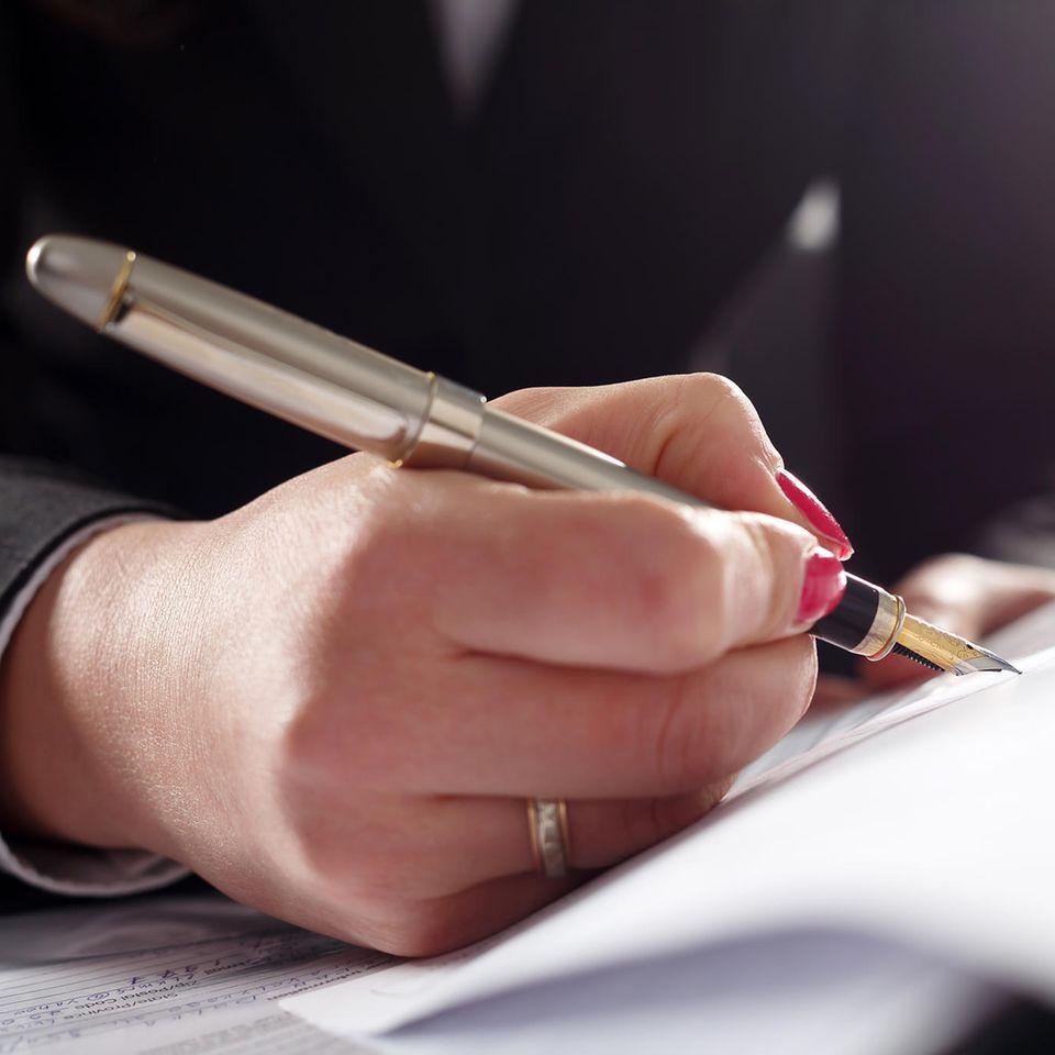 Frau schreibt Brief mit Füller