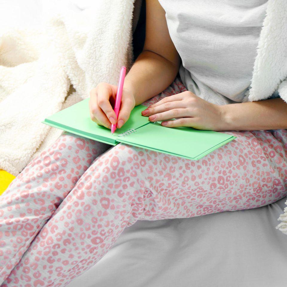 Langzeitkrank: Unterstützung beantragen und vorsorgen: Frau macht sich Notizen
