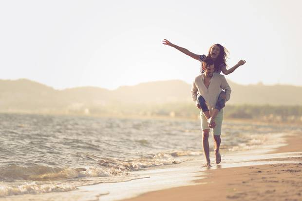 mann trägt Freundin am Strand auf dem Rücken