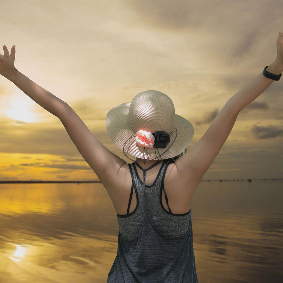 Frau mit Hut streckt Arme zum Himmel