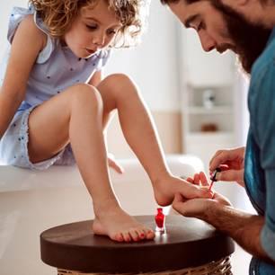 Moderne Väter: Vater lackiert Tochter die Fußnägel