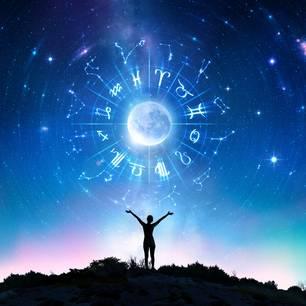 Horoskop: Ein Mensch streckt die Hände in den Himmel, in dem die Sternzeichen abgebildet sind