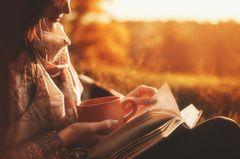 Frau liest Buch und trinkt Kaffee