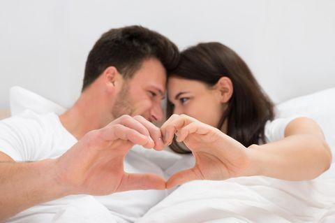 Verliebtes Paar im Bett formt Herz mit Händen