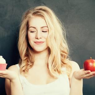 Horoskop: Eine Frau mit Apfel und Cupcake in jeweils einer Hand