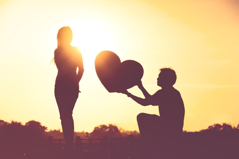 Horoskop: Ein Mann reicht einer Frau im Sonnenuntergang ein Herz