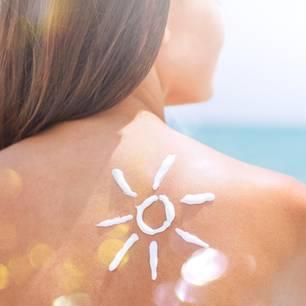 Frau mit Sonnencremesonne auf Schulter