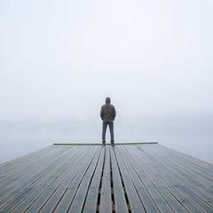 Mann auf Holzsteg bei Nebel