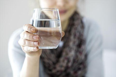 Frau hält ein Glas Wasser vor sich