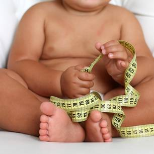 Dickes Baby mit Maßband in den Händen