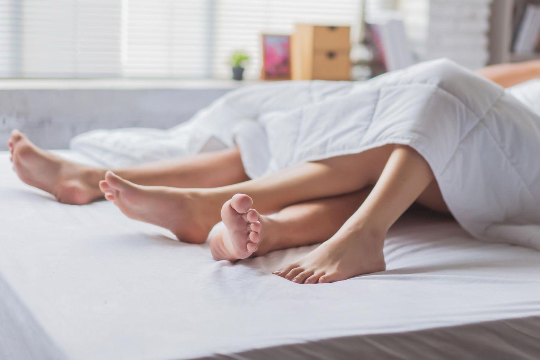 Beine von Paar im Bett