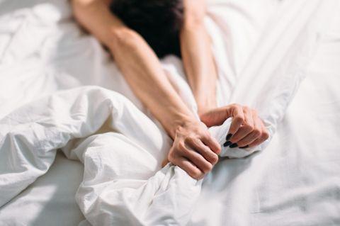 Horoskop: Eine Frau liegt im Bett und greift in die Decke