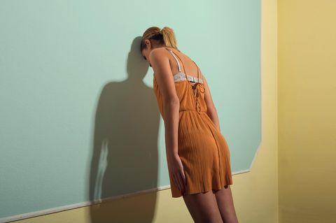 Frau lehnt mit Kopf gegen Wand