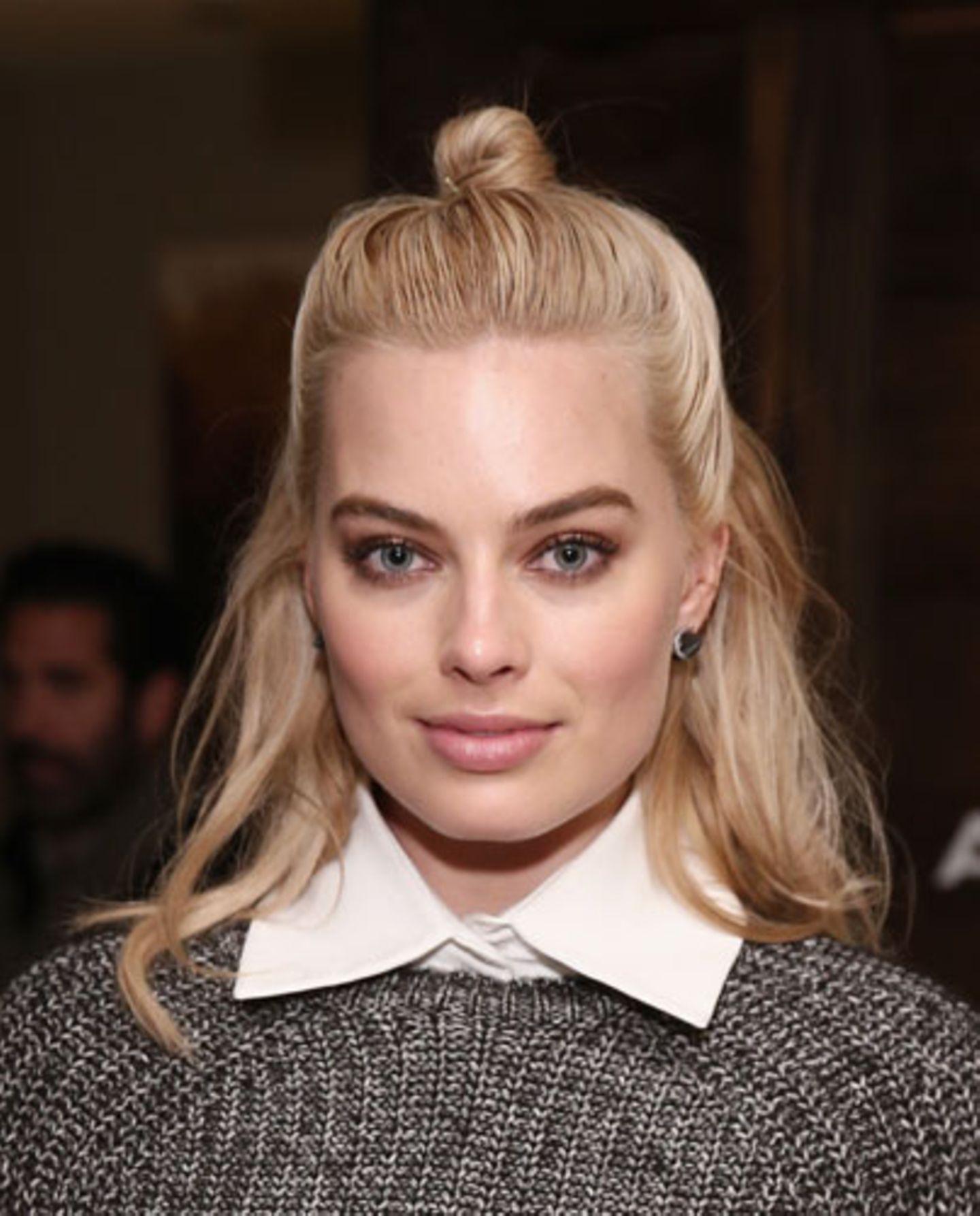 """Die australische Schauspielerin Margot Robbie trägt den """"Half Bun"""" in unserer Lieblingsvariante: Der Knoten sauber gestylt, der Rest der Haare leicht gewellt. Nicht zu schick, nicht zu lässig! Ein Styling, das sowohl für das Büro als auch für die Party funktioniert."""