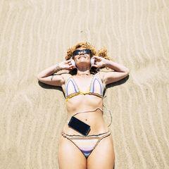 Care-Arbeit: Genug gekümmert! Frau liegt im Bikini am Strand