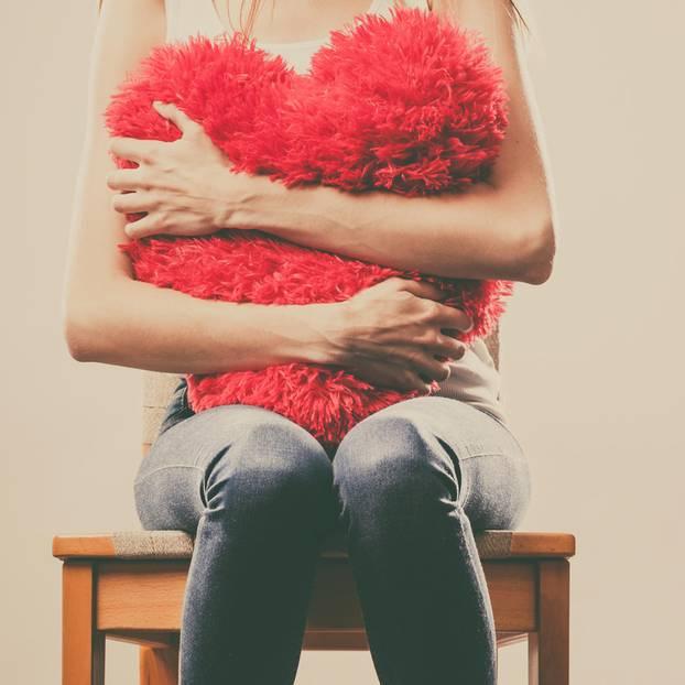 Horoskop: Eine Frau umklammert ein Herzkissen