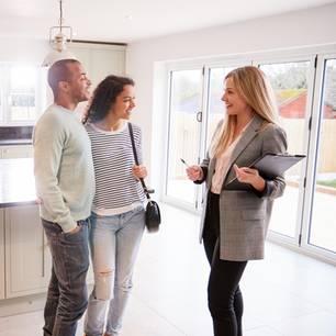 Immobilienmaklerin zeigt einem interessierten Pärchen ein Haus