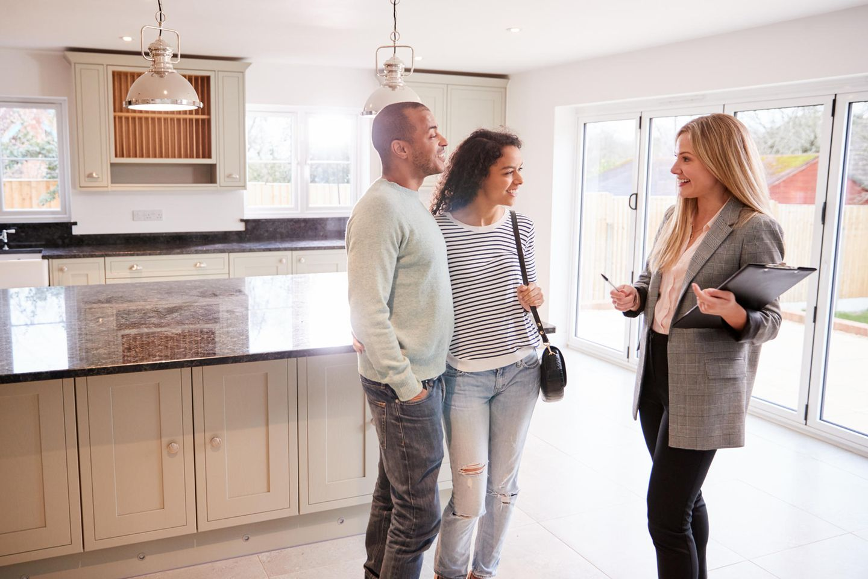 Immobilienmakler: Immobilienmaklerin zeigt einem interessierten Pärchen ein Haus