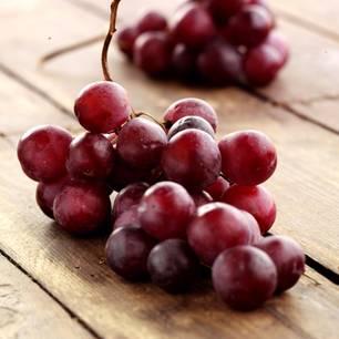 Rote Trauben auf Holztisch