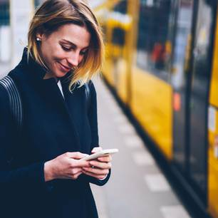 Nach dem ersten Date: Eine Frau schaut lächelnd auf ihr Handy