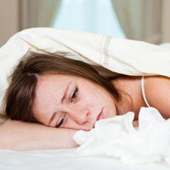 Erkältung und Depression: Die verschnupfte Seele: Frau liegt krank im Bett