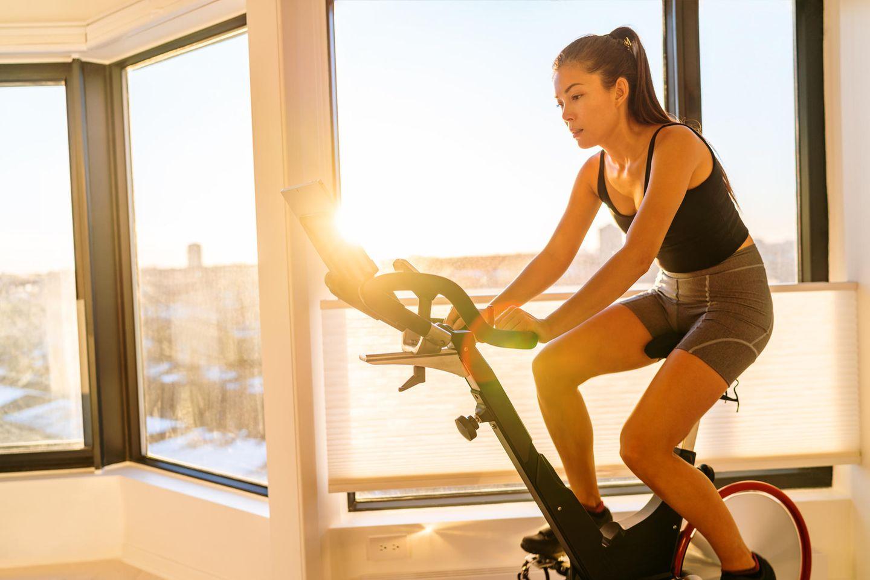 Peloton und Co: Bike-Trends für noch mehr Spaß: Frau auf Fitnessfahrrad