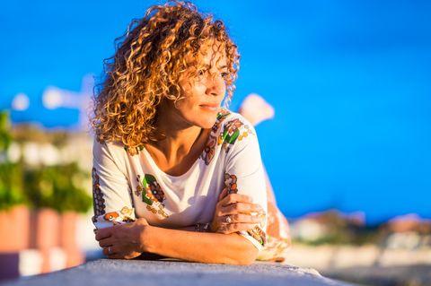 Wechseljahre und Rückenschmerzen: Jetzt wird's krumm: Frau liegt bäuchlings auf Mauer