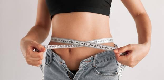 Abnehmen: Frau hält Maßband um ihren Bauch