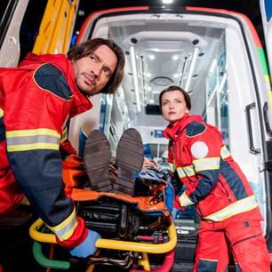 Zwei Rettungssanitäter schieben einen Verletzten auf einer Trage