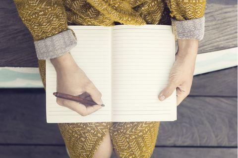 Dankbarkeitstagebuch: Frau mit Notizbuch auf dem Schoß
